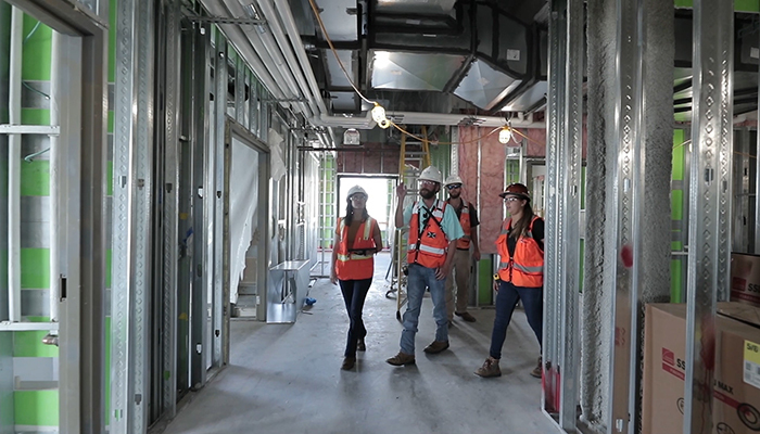 DPR's Daniel Berger walks his jobsite with other team members
