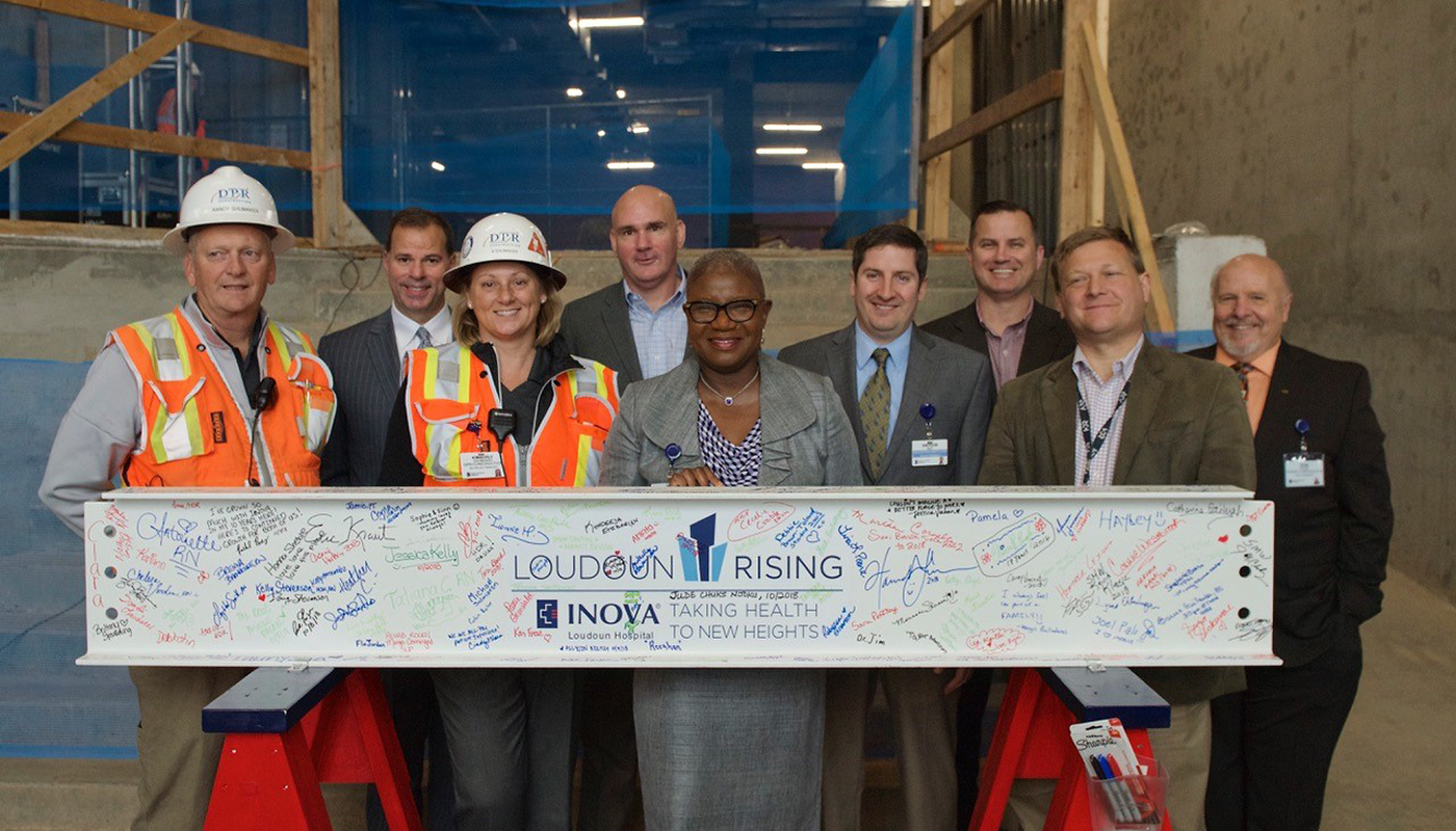 Design and construction team poses with signed beam alongside hospital CEO Deborah Addo.
